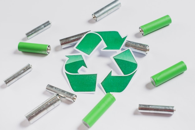 Recycle icon on batteries over white background
