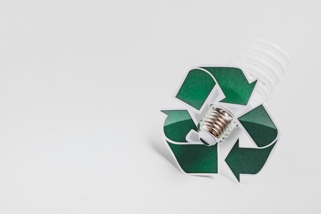 Recycle icon on compact fluorescent light bulb against white background