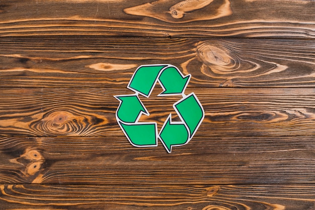 Recycle icon on wooden textured backdrop