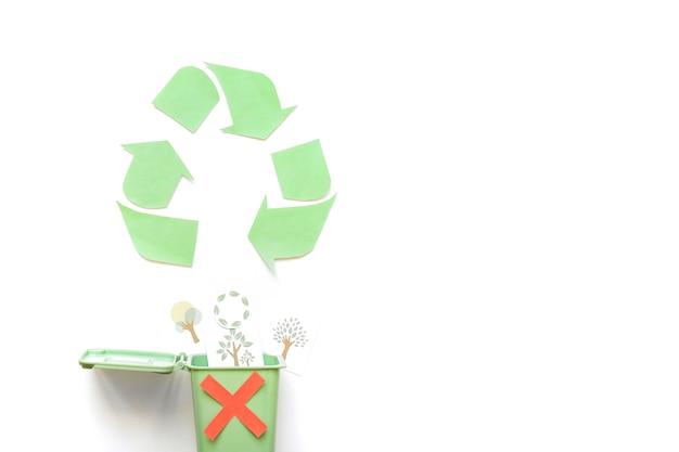 Ricicla il logo vicino al cestino con i disegni di verde