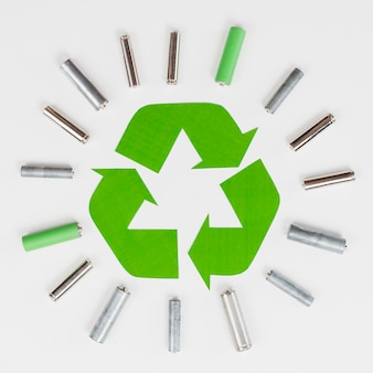 Recycle logo surrounded by trash batteries