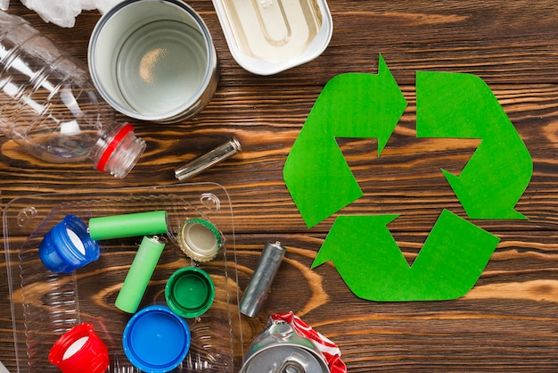 Recycle logo and various recyclable garbage on wooden desk