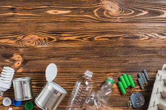 Recycle products arranged on bottom of wooden background