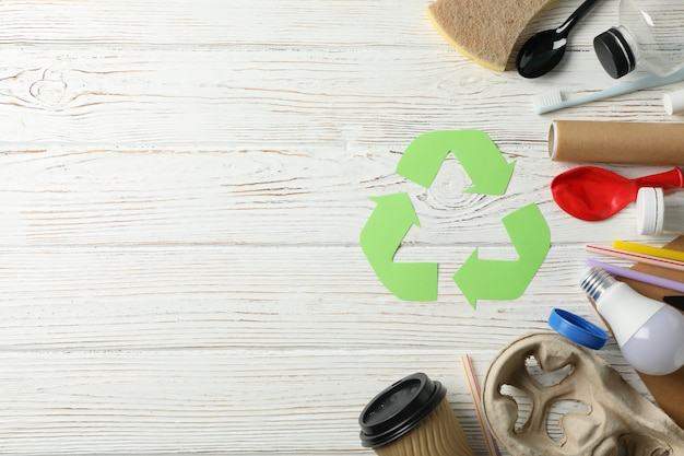 Recycle sign on wooden background with different trash, space for text
