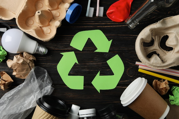 Recycle sign on wooden background with different trash, top view