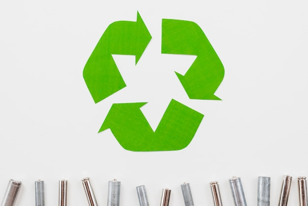 Recycle symbol and garbage batteries on grey background