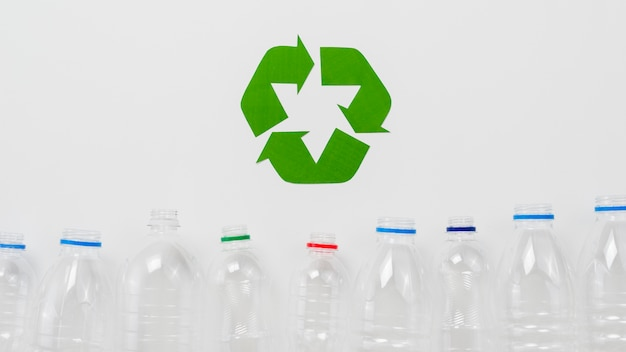 Recycle symbol and  plastic bottles on grey backgound