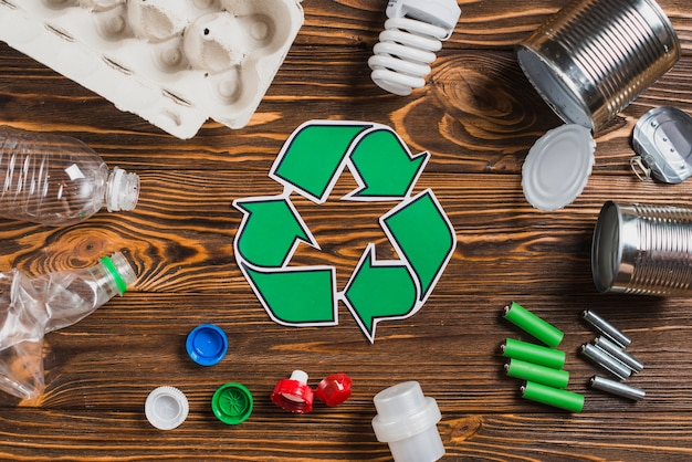 Recycle symbol surrounded with waste items on brown wooden textured background