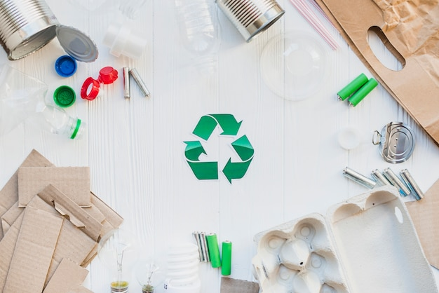 Recycle symbol with waste items on wooden white table