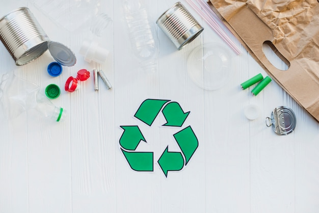 Recycle symbol with waste material on wooden table
