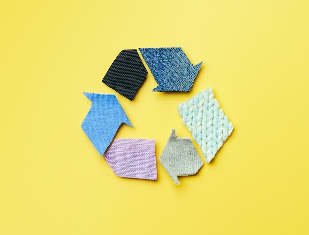 Повторное использование, уменьшение, переработка концепции фона. recycle символ из старой одежды на желтом фоне.