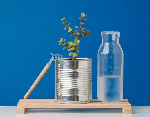 熊手と水を植える木の板に植物が付いているリサイクルされたアルミ缶
