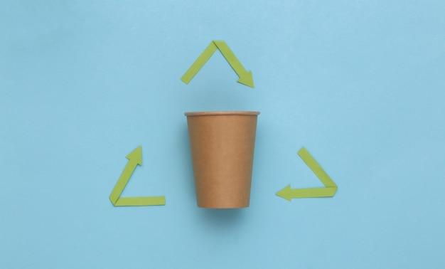 Рециркулированные стрелки знак и чашка кофе на синем фоне. эко-концепция. вид сверху
