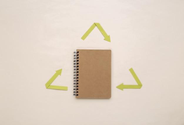 Рециркулированные стрелки знак и ноутбук на бежевом фоне. эко-концепция. вид сверху