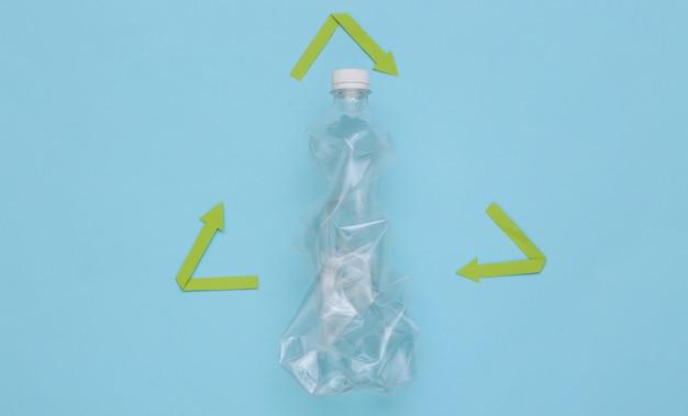 Переработанный знак стрелки и пластиковая бутылка на синем фоне. эко-концепция. вид сверху