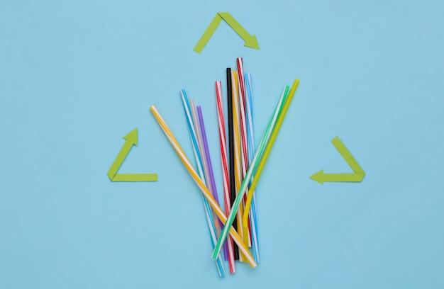 リサイクル矢印記号と青い背景の上のプラスチックカクテルストロー。エココンセプト。上面図