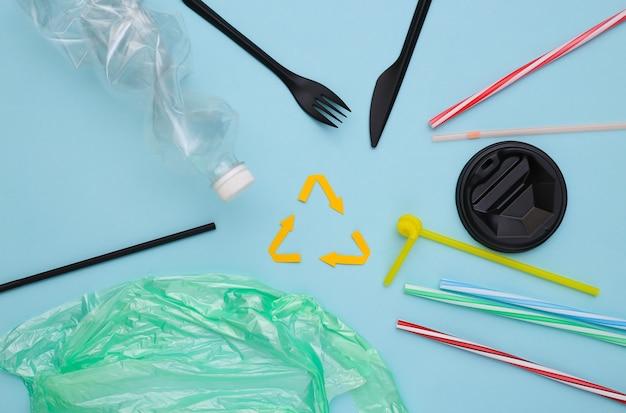 Переработанный знак стрелки и пластмассовые изделия на синем фоне. эко-концепция. спасти планету