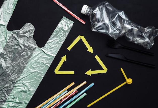Переработанный знак стрелки и пластмассовые изделия на черном фоне. эко-концепция. спасти планету. вид сверху