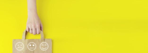 노란색 배경에 홀로그램 얼굴 감정 아이콘이 있는 재활용된 갈색 종이 쇼핑백이 평평하게 놓여 있습니다. 여름 판매 개념입니다. 배달 서비스 개념입니다.