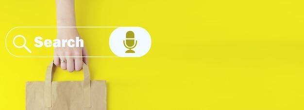 노란색 배경에 홀로그램 검색 주소 및 탐색 막대 아이콘이 있는 재활용된 갈색 종이 쇼핑백, 평평한 위치. 여름 판매 개념입니다. 데이터 검색 기술 검색 엔진 최적화.