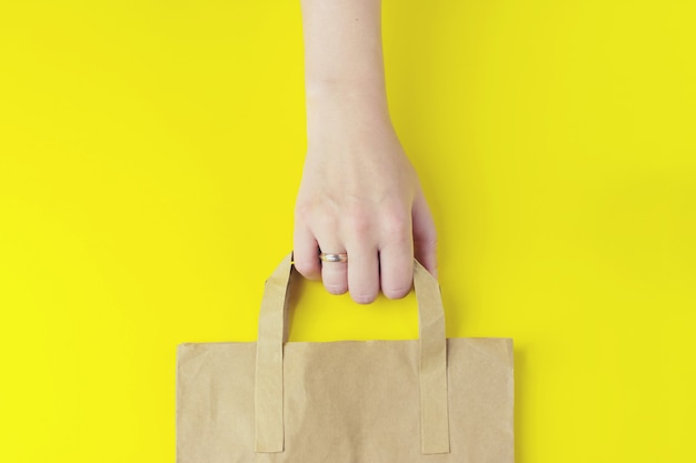 Recycled brown paper shopping bag with handle in hand on yellow background, flat lay, mockup