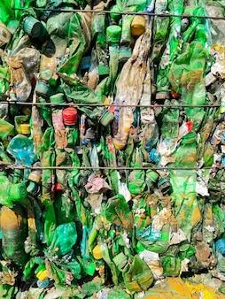 Переработанные использованные пластиковые бутылки в тюках на предприятии по переработке