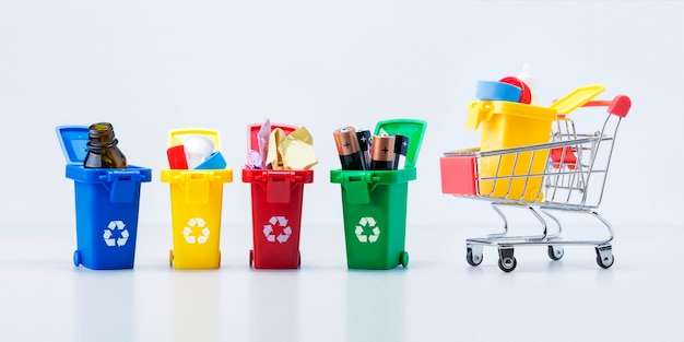 Recycling bin with plastic trash in small shopping cart and containers with garbage of  different types on grey surface. banner.