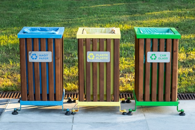 Recycling bins of different colors outdoors. garbage bin in the park, trash can on green grass background.