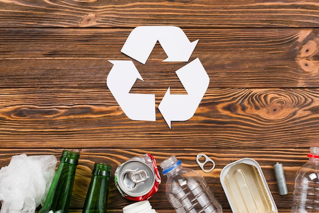 Recycling icon and trash on wooden background