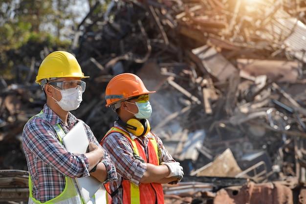 Промышленность по переработке отходов: работник, который перерабатывает вещи в центре переработки. менеджер и рабочий на полигоне металлических отходов.