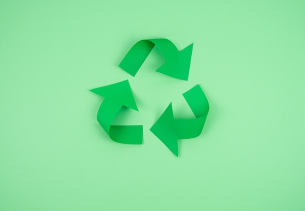 Recycling logo on green paper.