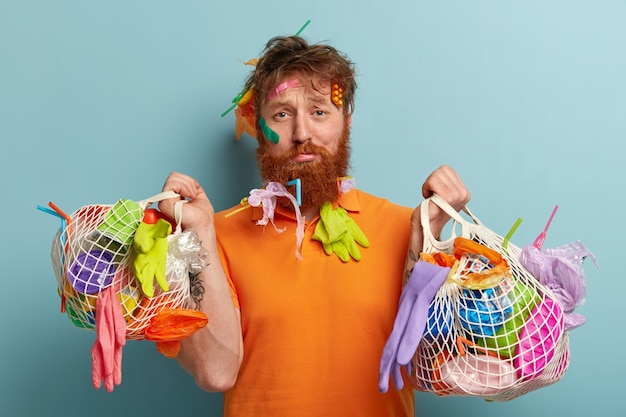 Recycling and plastic pollution problem concept. discontent redhead man with thick bristle, has rubbish stuck in hair and beard, carries two bags full of garbage, isolated over blue wall