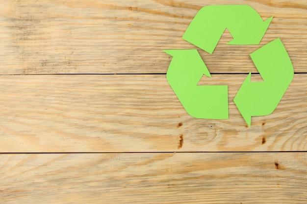 Знак переработки на натуральном деревянном столе. вид сверху. эко концепция