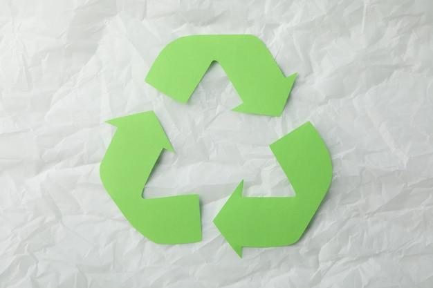 Утилизация знак на белом фоне мятой бумаги, вид сверху