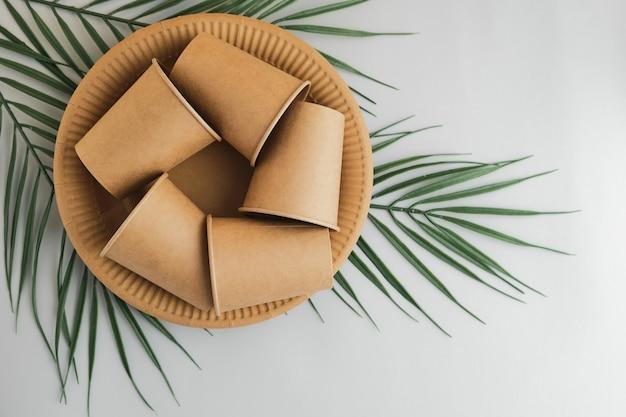 Символ переработки как концептуальный символ, сделанный из одноразовых картонных стаканов, тарелок на зеленых пальмовых ветвях