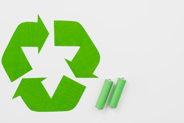 Recycling symbol beside green batteries