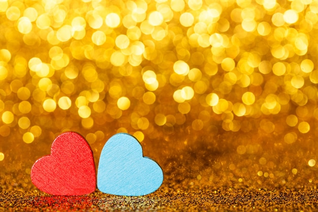 Red abd blue little decorative hearts against gold yellow sparkle glitter background with amazing bokeh lights. love or romantic valentine day concept. holiday background.