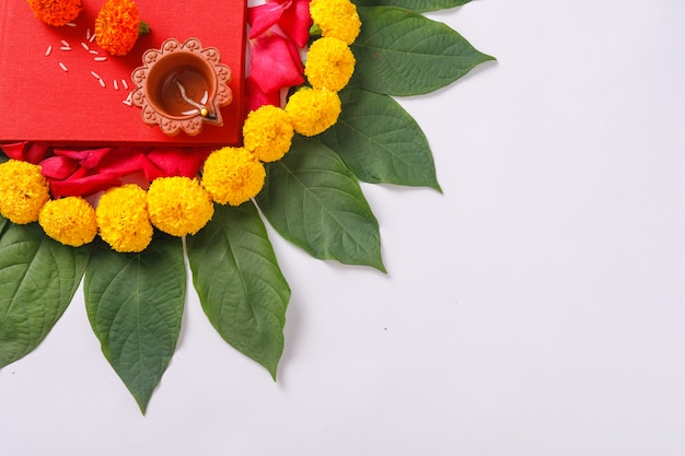 Red accounting notebook, diya, and flower rangoli on white