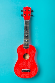 Red acoustic classic guitar on blue background