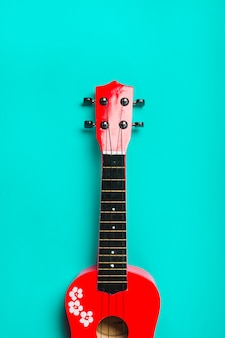 Red acoustic classic guitar on turquoise background