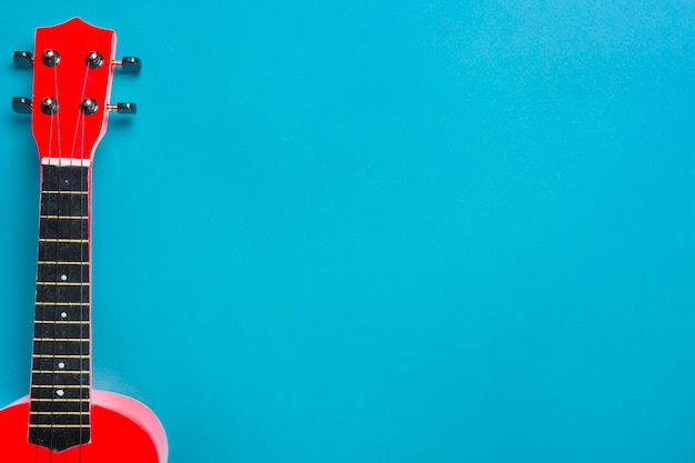 Красная акустическая гитара на синем фоне