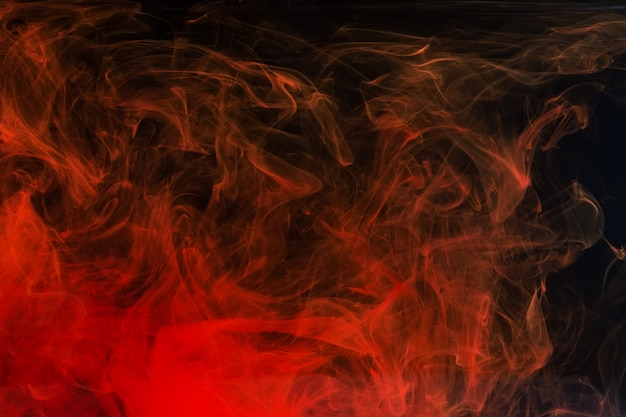 Red acrylic ink splashes in water on black backdrop.
