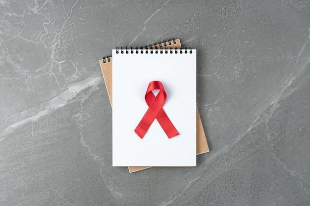 灰色の大理石のテーブル、上面図のノートに赤い援助リボン。 hivとエイズとの戦いの象徴、フラットレイ。