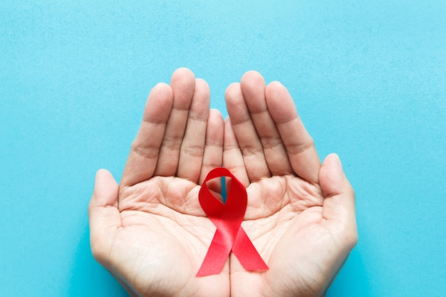 Red aids awareness ribbon on the hand. world aids day and healthcare and medicine concept