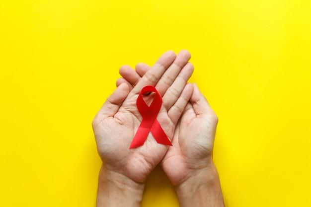 赤いエイズ認識リボン。世界エイズデーとヘルスケアと医学の概念