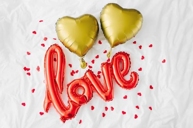 Красные воздушные шары в форме слова «любовь» с золотыми сердечками на кровати. концепция любви. праздник, торжество. день святого валентина или украшение свадьбы / девичника. воздушный шар из фольги