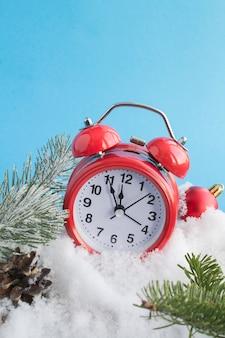 雪の背景に赤い目覚まし時計とクリスマスの構成。閉じる。