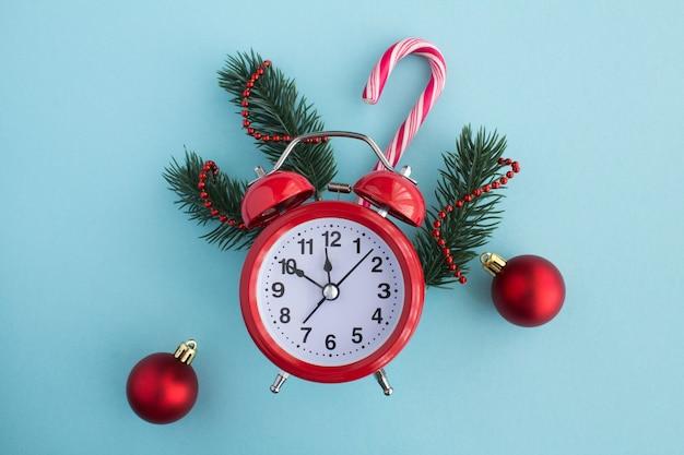 青い背景に赤い目覚まし時計とクリスマスの構成。上面図。コピースペース。