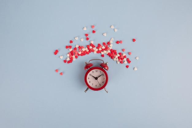 赤い目覚まし時計と青いテーブルの周りの赤いハート。