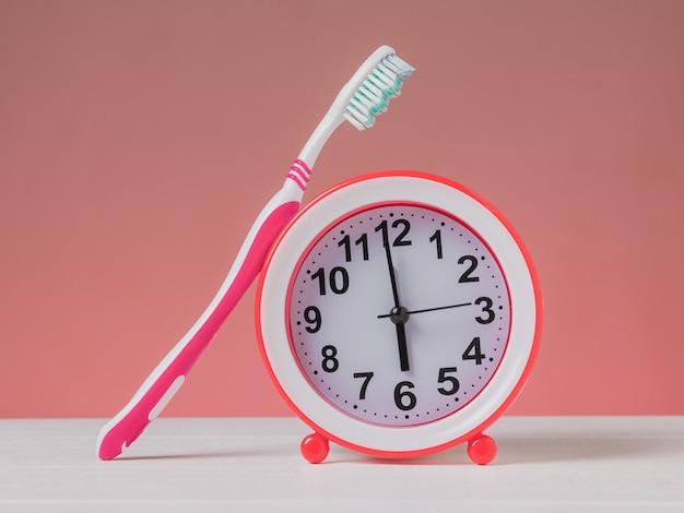 Красный будильник и красная зубная щетка на белом столе на розовом фоне. утренняя концепция. классические аналоговые часы.